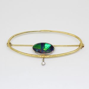 Solid boulder opal brooch set in 18ct yellow and white gold with diamond