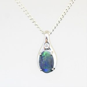 Solid black 0.47ct opal pendant set in 18ct white gold with diamond